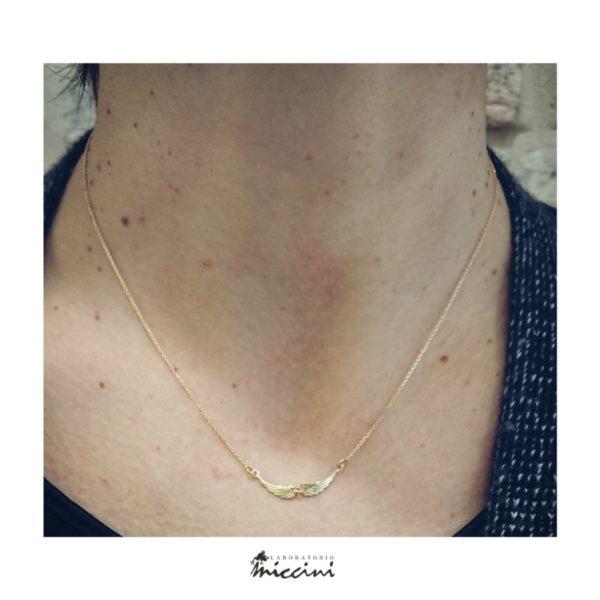 Collana ali in oro indossata